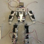 This photo shows an overhead view of a humanoid robot as it is being built from parts.